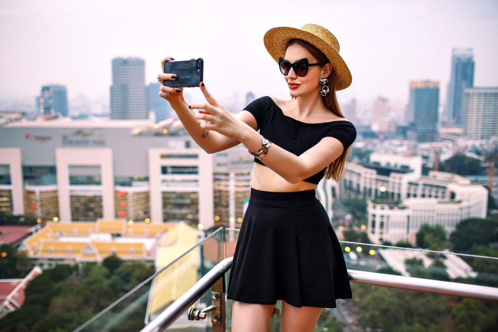 Young elegant woman wearing fashionable trendy summer outfit making touristic selfie at terrace of luxury hotel ,amazing view on whole Bangkok city, life at metropolis. Dream trip at Asia.